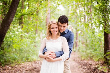 curare teneramente: Bella giovane coppia di nozze al di fuori in natura. Sposa in abito bianco e lo sposo in camicia jeans. Archivio Fotografico