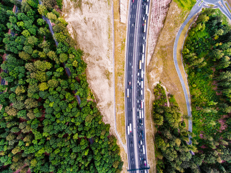 thoroughfare: Aerial view of highway full of cars and trucks, traffic jam in the middle of green forest, Netherlands