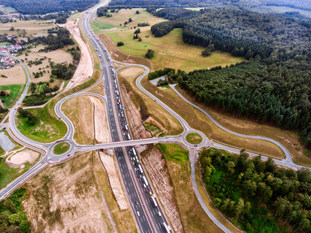 junctions: Aerial view of highway junction in the middle of green forest, traffic jam, Netherlands