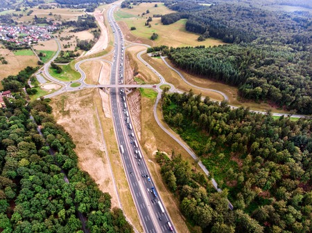 thoroughfare: Aerial view of highway junction in the middle of green forest, traffic jam, Netherlands