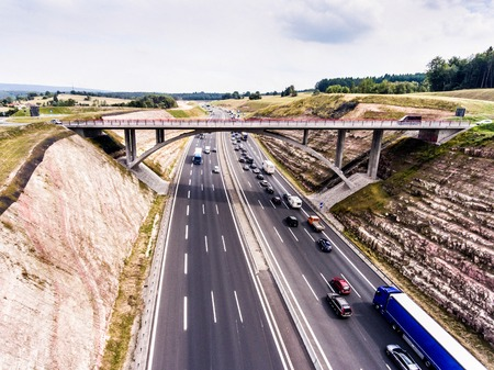 highway traffic: Aerial view of highway full of cars and trucks, traffic jam in the middle of green forest, Netherlands