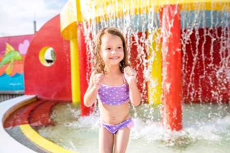Cute little girl in swimsuit having fun under splashing fountain, smiling. Summer heat and water.