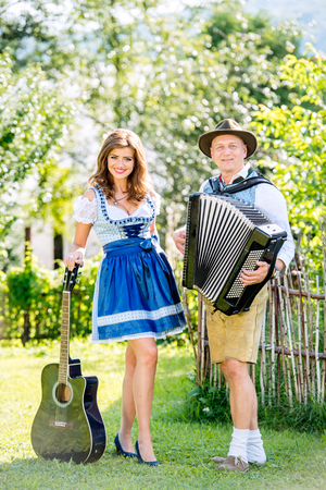 Couple in traditional bavarian clothes standing in the garden in front of wooden fence, playing accordion, holding guitar. Oktoberfest. Stock Photo