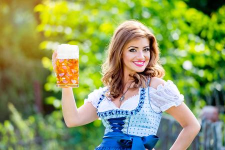 Schöne junge Frau in der traditionellen bayerischen Kleid, das im Garten einen Becher Bier. Oktoberfest.