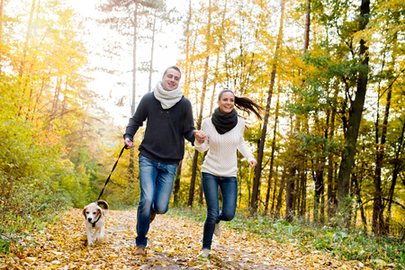 playful: Beautiful young couple with dog running in colorful sunny autumn forest Stock Photo