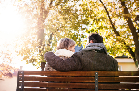couple nature: Senior couple sitting on bench, sunny autumn nature. Rear view