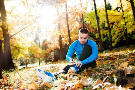 cross ties: Young handsome hipster runner in blue sweatshirt outside in colorful sunny autumn nature sitting on the ground, tying shoelaces