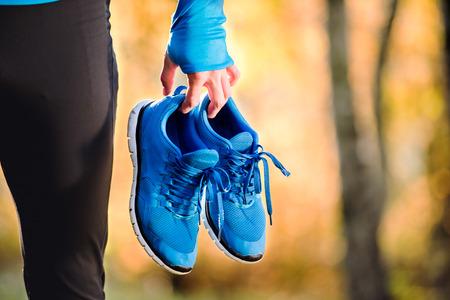 Nierozpoznany biegacz niebieska bluza trzymającego parę butów sportowych na zewnątrz w słoneczny jesienny kolorowe charakter.