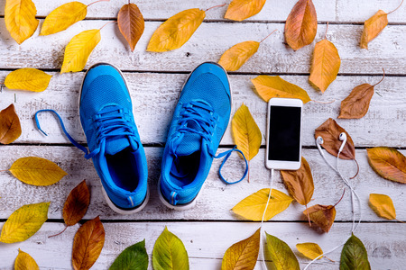 Blue sports shoes. Smart phone, earphones, colorful autumn leaves. Studio shot on white wooden background.