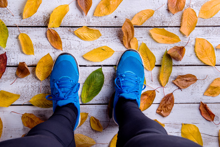 running pants: Legs of runner. Blue sports shoes. Colorful autumn leaves. Studio shot on white wooden background. Stock Photo