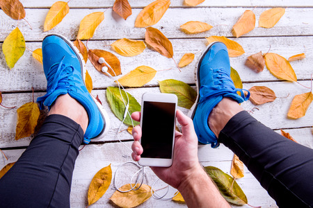 Legs of unrecognizable runner in blue sports shoes. Smart phone and earphones. Colorful autumn leaves. Studio shot on white wooden background. Stock Photo