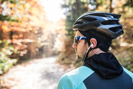 Young handsome sportsman riding his bicycle outside in sunny autumn nature, earphones in his ears, rear view