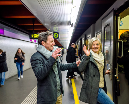 platforms: Beautiful senior couple standing at the underground platform, entering the train
