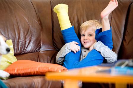 Ragazzino sveglio biondo con gamba rotta in ghisa seduto sul divano in pelle, sorridente, gli occhi chiusi. divertimento diurno per bambini. Felice di essere a casa.