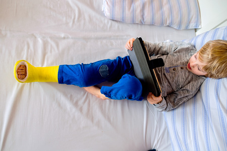 Little boy with broken leg lying in bed playing on tablet
