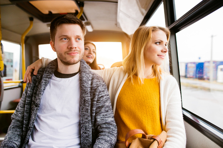 looking out: Beautiful young couple traveling by bus, looking out of window, having fun in town. Stock Photo