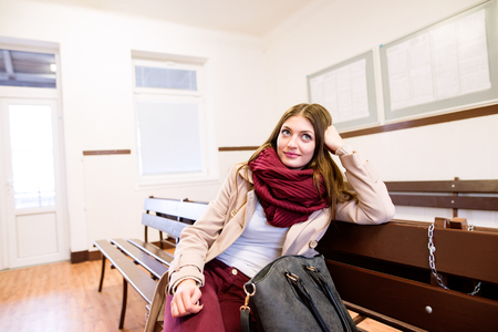 buss: Beautiful young woman traveling, sitting in bus waiting room, having fun in town.