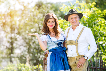 lederhosen: Couple in traditional bavarian clothes standing in the garden in front of wooden fence. Oktoberfest. Stock Photo