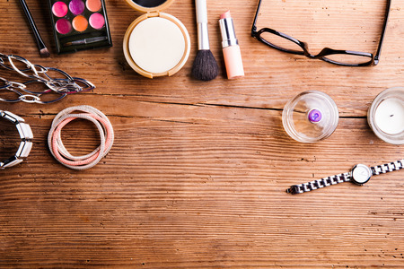 Various make up products laid on table. Studio shot on wooden background. Flat lay, copy space.