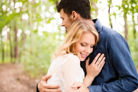 curare teneramente: Bella giovane coppia di sposi fuori nella foresta verde. Sposa in abito bianco e lo sposo in camicia jeans. Archivio Fotografico