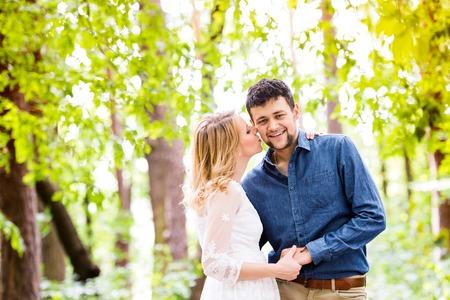 pareja de esposos: Pares de la boda hermosa joven fuera de bosque verde. Novia en vestido blanco que besa a su novio en camisa de mezclilla.