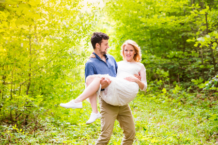Beautiful young wedding couple outside in green forest. Groom carrying his bride in his arms.