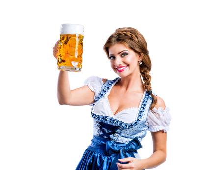 octoberfest: Mujer joven hermosa en alineada bávara tradicional que sostiene una jarra de cerveza. Oktoberfest. Foto de estudio sobre fondo blanco, aislado.