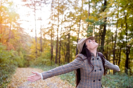 Beautiful young woman with long hair in checked coat and brown hat in autumn forest, arms stretched, smiling Stock Photo