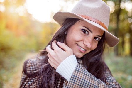 stylish hair: Beautiful young woman in checked coat and brown hat in autumn forest