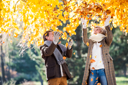 walk in: Active senior couple on a walk in autumn park throwing leaves