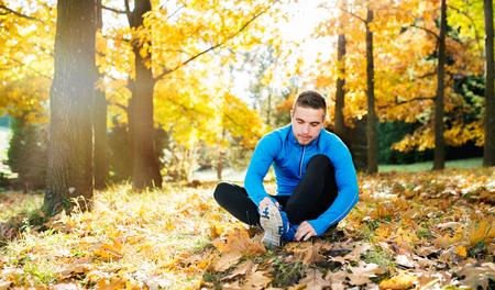 atletismo: Corredor joven hermoso hipster en camiseta azul en el exterior en la naturaleza colorida soleado de otoño sentado en el suelo, atarse los cordones Foto de archivo