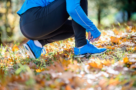 colourful tie: Unrecognizable runner in blue sweatshirt outside in colorful sunny autumn nature sitting on the ground, tying shoelaces