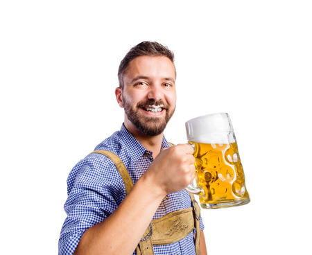 Handsome young man in traditional bavarian clothes holding a mug of beer, drinking from it, having foam on his upper lip. Oktoberfest. Studio shot on white background, isolated.
