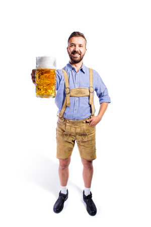 Handsome young man in traditional bavarian clothes holding a mug of beer. Oktoberfest. Studio shot on white background, isolated.