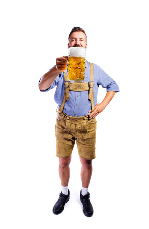 lederhosen: Handsome young man in traditional bavarian clothes holding a mug of beer. Oktoberfest. Studio shot on white background, isolated.