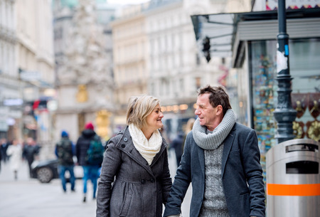 walk in: Beautiful senior couple on a walk in historical centre of the city of Vienna, Austria. Winter.