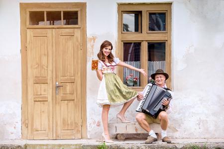 puertas de madera: Pareja en la ropa tradicional de Baviera que se opone antigua casa de campo, hombre tocando el acordeón, la mujer que sostiene una jarra de cerveza. Oktoberfest.