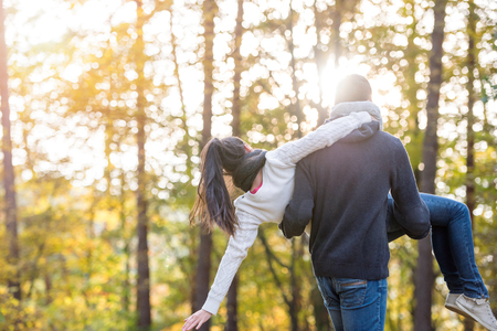 man carrying woman: Beautiful young couple in love, man carrying woman in his arms, rear view. Autumn forest, sunny day.