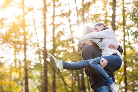 Beautiful young couple in love kissing, man carrying woman in his arms. Autumn forest, sunny day.