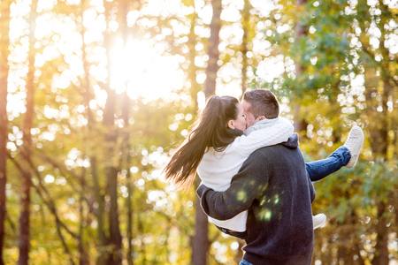 Beautiful young couple in love kissing, man carrying woman in his arms. Rear view. Autumn forest, sunny day.