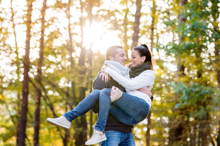 Beautiful young couple in love, man carrying woman in his arms. Autumn forest, sunny day. Stock Photo