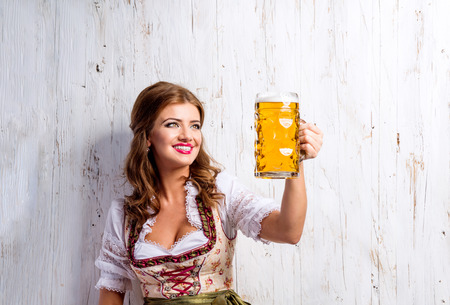 german: Beautiful young woman in traditional bavarian dress holding a mug of beer, clinking. Oktoberfest. Studio shot on white wooden background. Stock Photo