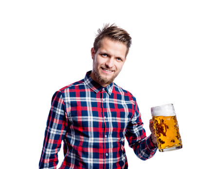 clinking: Handsome young hipster man in checked shirt holding a mug of beer, clinking. Oktoberfest. Studio shot on white background, isolated.