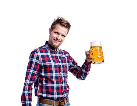 hombre tomando cerveza: hombre inconformista joven en camisa a cuadros que sostiene una jarra de cerveza, chocan. Oktoberfest. Foto de estudio sobre fondo blanco, aislado.