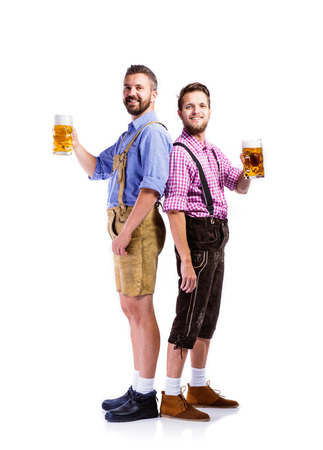white men: Two handsome hipster young men in traditional bavarian clothes holding mugs of beer, clinking. Oktoberfest. Studio shot on white background, isolated.