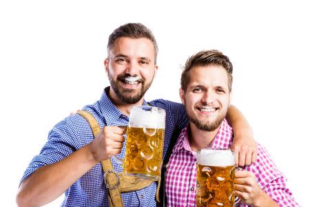 2 つハンサムな流行に敏感な若い男性のビール、ジョッキを保持伝統的なバイエルン衣服チャリンします。オクトーバーフェスト。分離の白い背景で