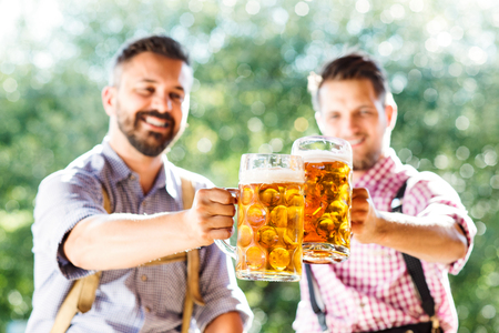 lederhosen: Two handsome hipster young men in traditional bavarian clothes holding mugs of beer, clinking. Oktoberfest. Sunny summer garden. Stock Photo