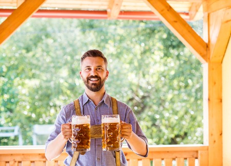 lederhosen: Handsome hipster young men in traditional bavarian clothes holding two mugs of beer. Oktoberfest. Sunny summer garden. Stock Photo
