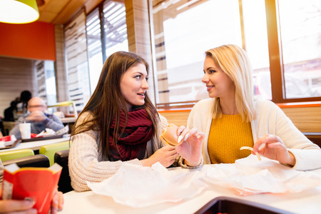 fast food restaurant: Two beautiful young women eating out in fast food restaurant, talking, having fun