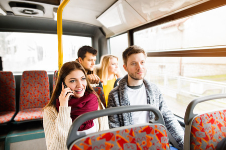 buss: Group of young people traveling by bus, having fun in town. Girl talking on phone.